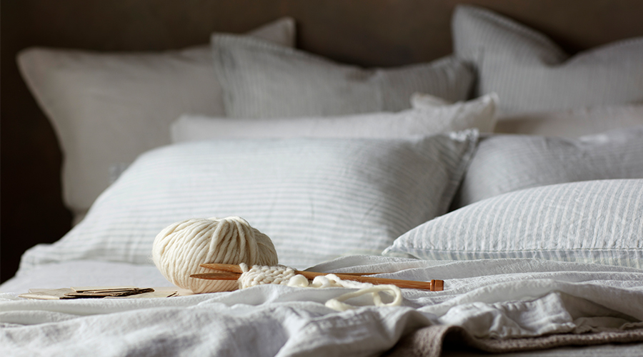A Ball of Yarn on Top of Our Sage Stripe Linen Bedding
